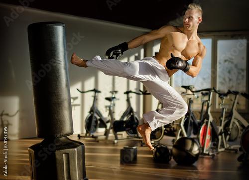 Shirtless young man doing flying kick