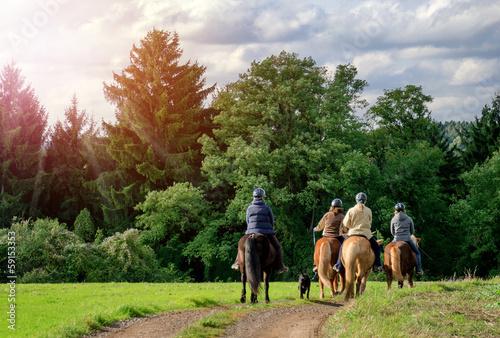 Spoed Foto op Canvas Paardrijden Idyllischer Ausritt - Gruppe Reiter Pferde - Horse Riding