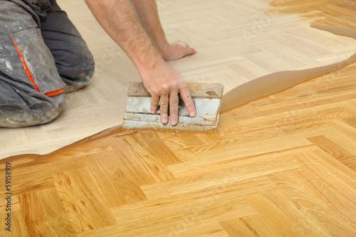 Fototapeta Home renovation varnishing oak parquet floor worker hand, tool obraz na płótnie