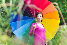 Beautiful Young Pregnant Woman Walking Under A Colorful Umbrella