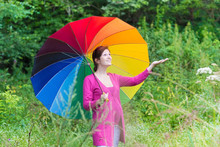 Attractive Pregnant Woman Walking Under A Colorful Umbrella