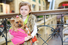 Little Cute Girl Holds Bag With Small Dog Stands