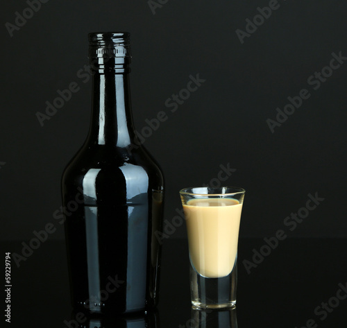 Baileys liqueur in bottle and glass isolated on black Poster