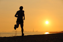 Backlight Of A Man Running On The Beach At Sunset