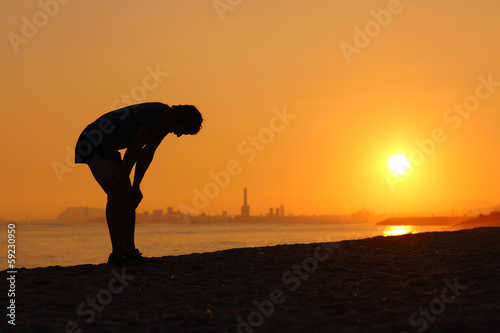 Fotografie, Obraz  Silhouette of an tired sportsman at sunset