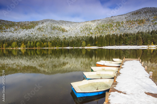 Photo  Snowy pier and boats on the lake,St Ana lake,Transylvania,Romani