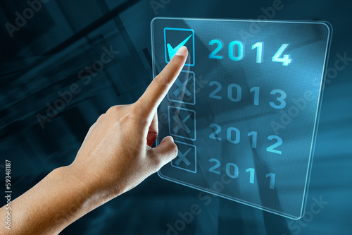 Poster  A woman hand selects 2014 on a digital screen