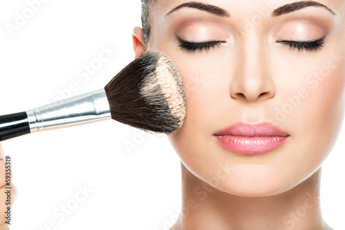 Obraz woman  applying dry cosmetic tonal foundation  on the face - fototapety do salonu