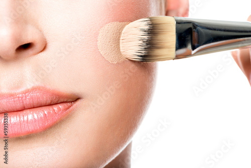 Makeup artist applying liquid tonal foundation  on the face Plakat