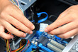 Closeup of a technician's hands wiring a computer mainboard