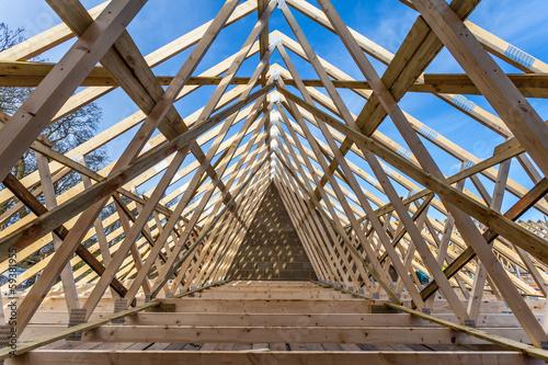 Wood house truss against blue sky Canvas Print