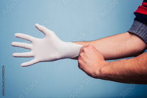Fotografija  Man putting on latex surgical glove