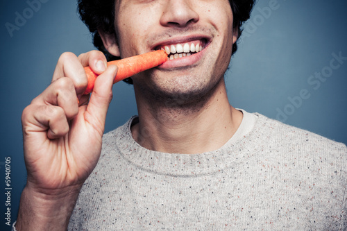 Photo  Young man eating a carrot