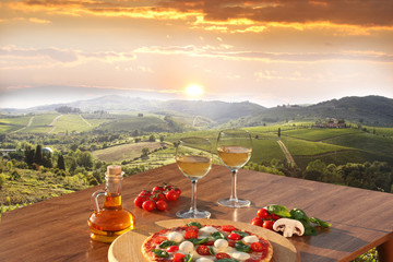 FototapetaItalian pizza and glasses of white wine in Chianti, Italy