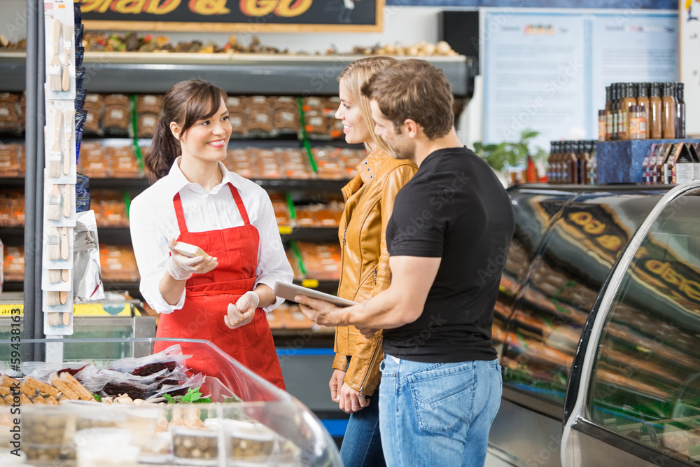Fototapeta Saleswoman Assisting Couple In Buying Meat
