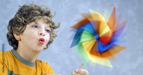 blonde child blowing a pinwheel Fototapet