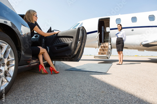 Wealthy Woman Stepping Out Of Car At Terminal Fototapeta