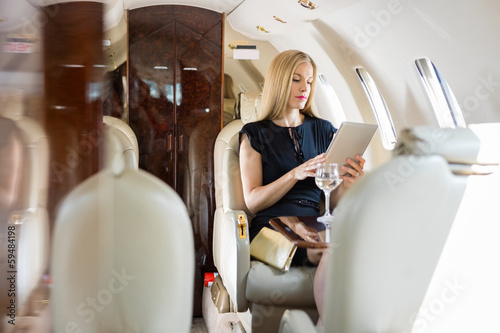 Valokuvatapetti Woman Using Tablet Computer In Private Jet