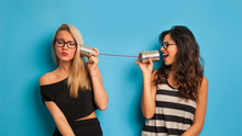 Blonde And Brunette Women Talking With Tin Can Telephone Against
