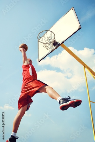 Fotografiet  Basketball player in action flying high and scoring