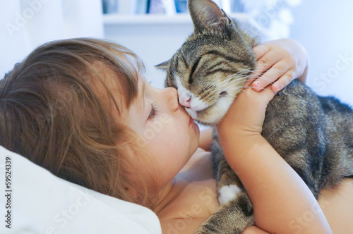 Photo  Child is kissing a cat