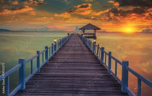 Obraz Drewniany most w pięknej scenerii zachodzącego słońca - fototapety do salonu