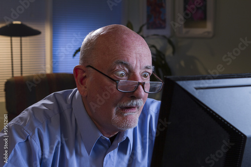 Photo  Man is shocked with information on his computer, horizontal