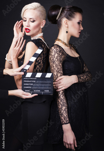 Fotografia, Obraz  two beautiful girl in retro style with clapperboard
