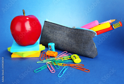 Fotografía pencil box with school equipment on blue background