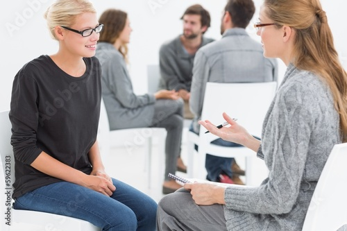 Group therapy session with therapist and client in foreground Fototapete