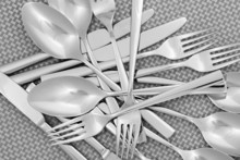 Forks, Knifes And Spoons On Grey Mat Close-up