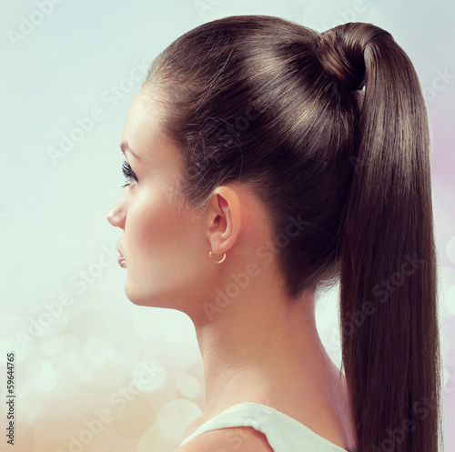 Young female with healthy shining brown hairs put in pony tail. Wall mural