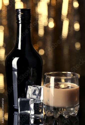 Spoed Foto op Canvas Bar Baileys liqueur in bottle and glass on golden background