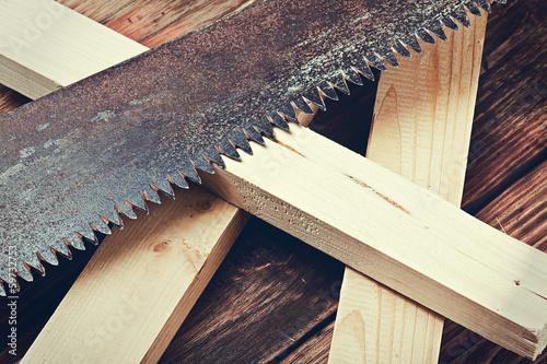 Fototapeta metal saws and sawn timber on the table. Focus on the teeth of t obraz na płótnie