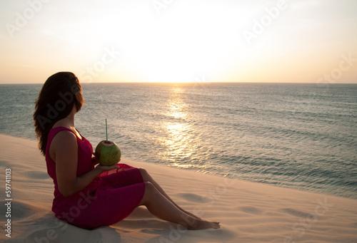 Junge hübsche Frau sitzt auf Düne am Meer - Sonnenuntergang