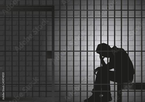 Fototapeta Concept de la prison et de l'arrestation d'un délinquant ou d'un criminel, avec un prisonnier qui assis dans sa cellule qui se tient la tête dans les mains