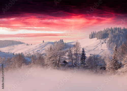 Poster Morning with fog Foggy winter landscape in mountain village ander the dark red s