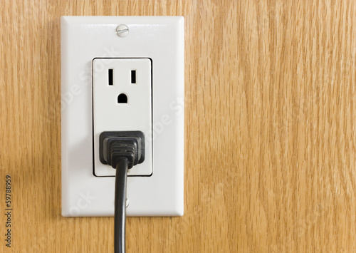 Electrical Outlet With Black Cord On Wood Grain Wall