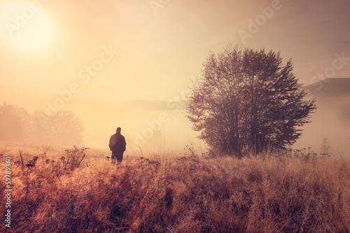Cadres-photo bureau Brun profond Lonely person in the morning mist. Landscape composition.