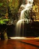 Small waterfall  on fresh stream, water  run over mossy  block