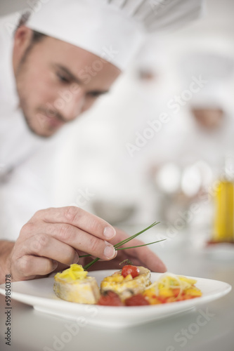 Fotografía  closeup on chef's hands garnishing a plate