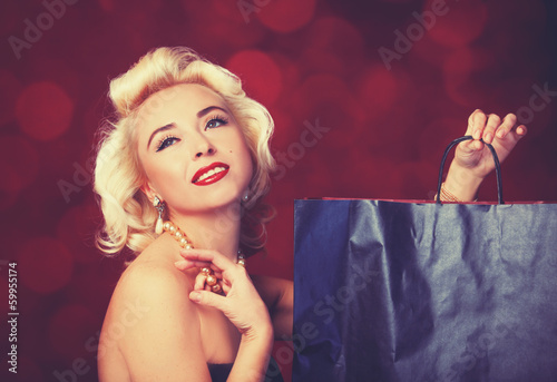 Photo  Pretty blond girl model like Marilyn Monroe with shopping bag