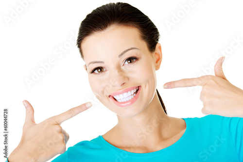 Fotografia  Beautiful woman pointing on her perfect white teeth.