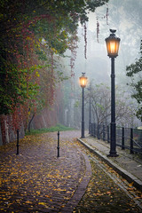 Fototapeta Uliczki The mysterious alleyway in foggy autumn time with lighted lamps
