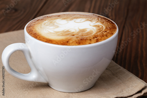 Fotografija freshly made cup of cappuccino with abstract latte art