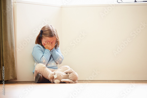 Fotografie, Tablou  Unhappy Child Sitting On Floor In Corner At Home