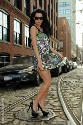 Photo  Young brunette standing on old tram rails at Dumbo area
