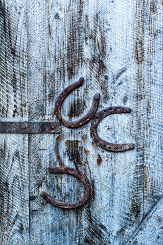 zardzewiale-podkowy-na-drewniane-stare-drzwi-tlo