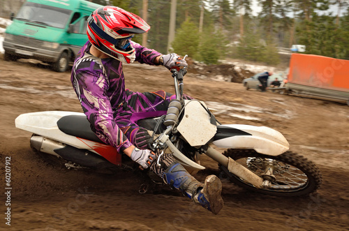 Foto op Plexiglas Motorsport Motocross athlete raised leg forward executes turning