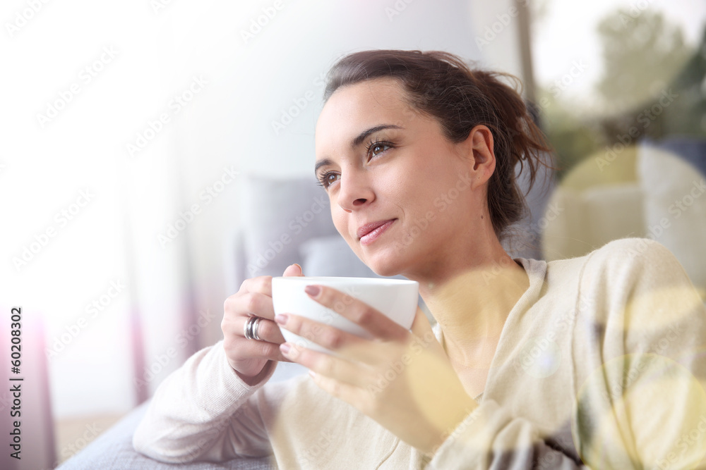 Fototapeta Peaceful woman relaxing at home with cup of tea